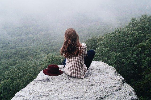 崖の上に座る女性の後ろ姿